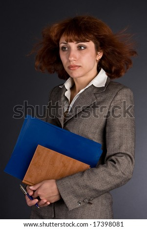 The woman with folders in office business suit - stock photo