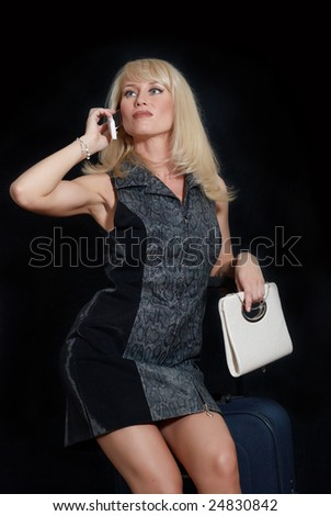 The woman with mobile phone, female handbag and suitcase
