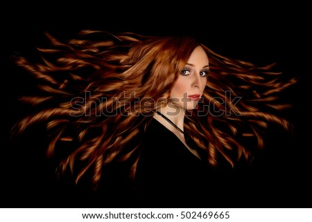 the woman with red curly long hair looks in the camera on black background