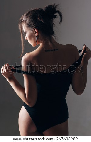 The woman with tatoo  in a sports swimsuit. - stock photo