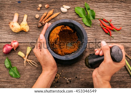 The Women hold pestle with mortar and spice red curry paste ingredient of thai popular food on rustic wooden background. Spices ingredients chilli ,pepper, garlic,lemongrass and kaffir lime leaves .