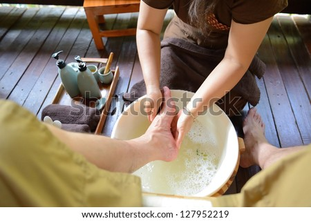 The women is washing his foot to prepare for thai spa foot massage - stock photo