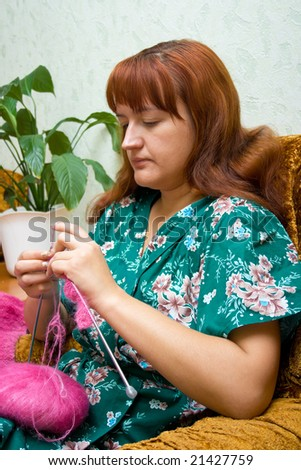 The women knits on spokes a thing, sitting on an armchair in a room