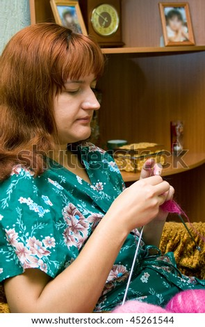 The women knits on spokes a thing, sitting on an armchair in a room. Shallow DOF