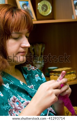 The women knits on spokes a thing, sitting on an armchair in a room. Shallow DOF, focus on hands