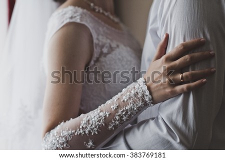 The womens hands embrace the mans shoulder.