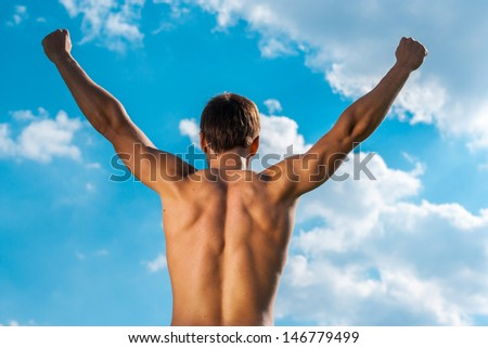 the won person with the raised hands against the sky. view from a back - stock photo
