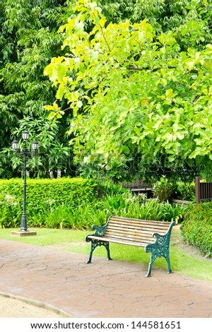 The wood bench in a tropical park - stock photo