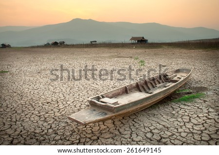 The wood boat on cracked earth, metaphoric for climate change and global warming. - stock photo