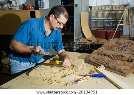 The woodcarver work in the workshop. - stock photo