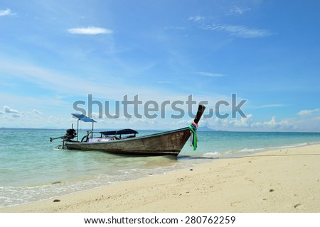 The wooden boat on a beach with blue transparent water. And under blue clouds.
