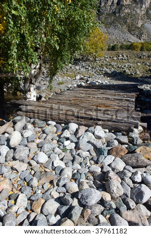 The wooden bridge from logs through mountain small river