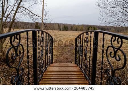 The wooden bridge through a creek. Hand-forged railings. Backyard of Holy Trinity Church. - stock photo
