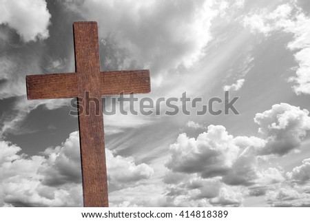 The wooden brown cross of Jesus Christ against black and white clouds background