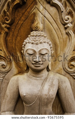 The wooden Buddha statue is smiling with mercy. - stock photo