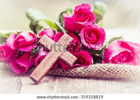 The wooden cross and pink roses on wooden  background, burred background - stock photo