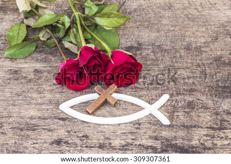 The  wooden  cross  over the white christian fish and red roses  on wooden background, world mission concept.  - stock photo
