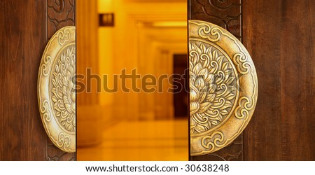 The wooden door decorated with luxury handle  stood ajar in the buddhist temple. - stock photo