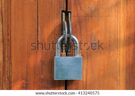 The wooden door is locked by a metal padlock at the afternoon