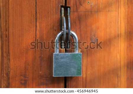 The wooden door is locked by a metal padlock at the morning