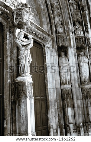 The wooden doors and statues of Cathedrale Sainte Sauveur in Aix-en-Provence, France - Black and white with blue cast - duotone - stock photo