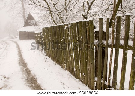 The wooden fence along the countryside road in cold winter, Slovakia - stock photo