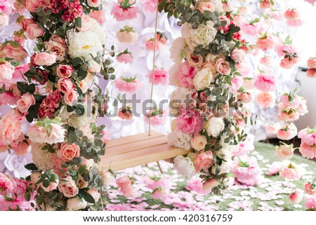 The wooden swing decorated with artificial flowers - stock photo