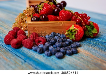 The wooden table laid out in the form of fresh fruits, strawberries, raspberries, currants, cherries - stock photo