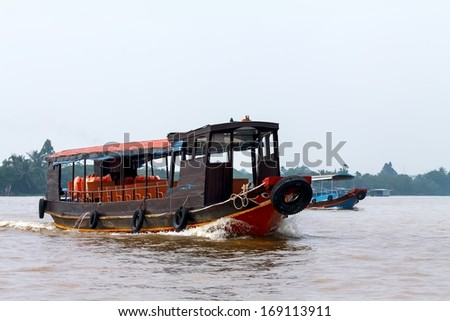 The wooden tourist boat on (Mekong) River