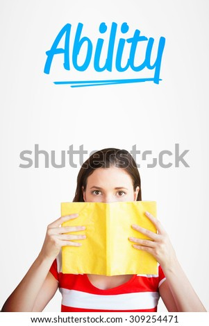 The word ability and student covering face with book in library against white background with vignette - stock photo