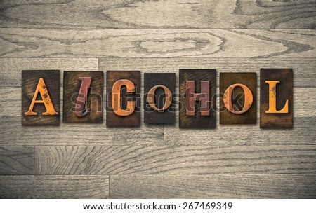 "The word ""ALCOHOL"" theme written in vintage, ink stained, wooden letterpress type on a wood grained background. - stock photo"