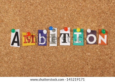 The word Ambition in cut out magazine letters pinned to a cork notice board
