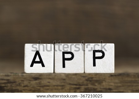 The word app written in cubes on wooden background