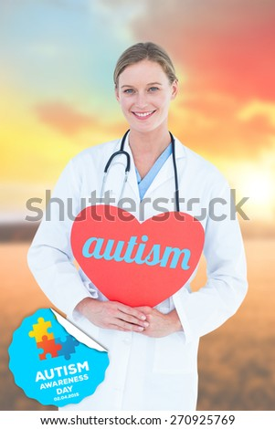 The word autism and doctor holding red heart card against countryside scene - stock photo