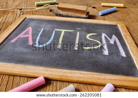 the word autism written with chalk of different colors in a chalkboard placed on a rustic wooden desk or table - stock photo