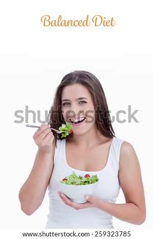 The word balanced diet against smiling young woman eating a salad
