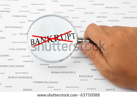 The word BANKRUPT with red cross is magnified. - stock photo