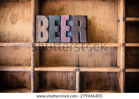 The word BEER written in vintage wooden letterpress type in a wooden type drawer. - stock photo