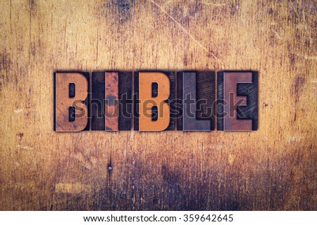 """The word """"Bible"""" written in dirty vintage letterpress type on a aged wooden background. - stock photo"""