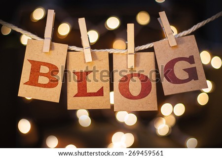 The word BLOG spelled out on clothespin clipped cards in front of glowing lights. - stock photo
