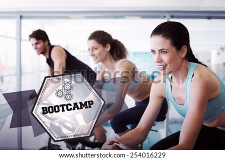 The word bootcamp and fit people in a spin class against hexagon - stock photo