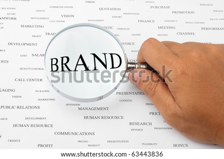 The word BRAND is magnified. - stock photo
