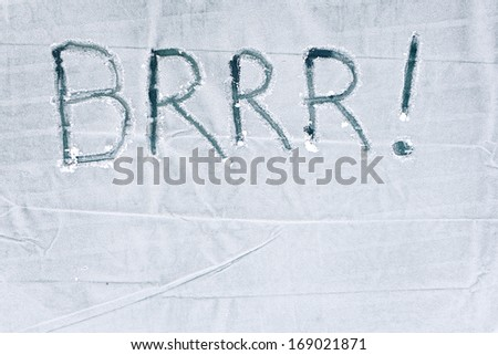 "The word ""BRRR!"" handwritten in frost on a canvas background."