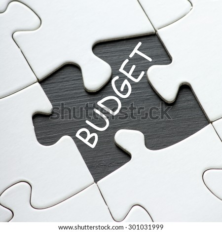 The word Budget in white text on a blackboard as revealed by a missing piece from a jigsaw puzzle - stock photo