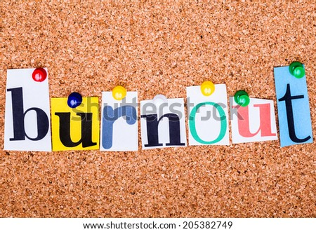 The word Burnout in cut out magazine letters pinned to a cork notice board with push pins - stock photo