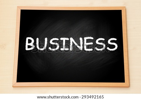 The word 'Business' on black chalkboard with wooden frame on wood background. - stock photo