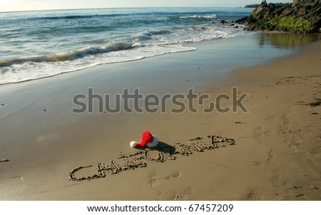 """the word """"California"""" written in the wet sand on a southern california beach with a """"Santa Hat""""  and a blue sky and nice tide and waves from the pacific ocean - stock photo"""