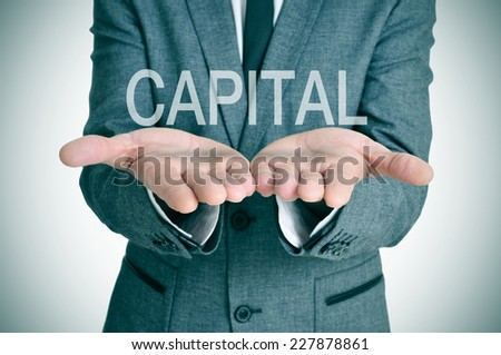 the word capital in the open hands of a businessman - stock photo
