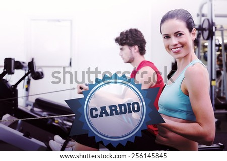 The word cardio and smiling brunette working out on the rowing machine against badge - stock photo