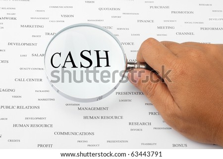 The word CASH is magnified. - stock photo